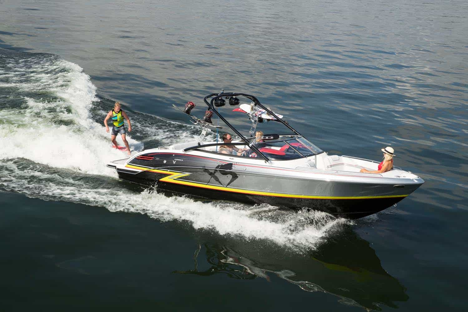 An image of the 270 Xtreme Sport boat on the ocean for better understanding of the model visually. Shows a smaller boat with the letters XS painted in black on the side of the boat. A man is wake boarding behind the boat while three other people sit in the boat.